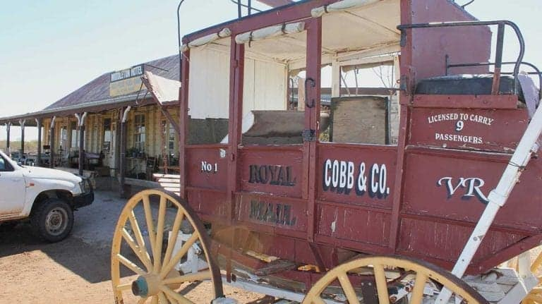Old maroon Cobb & Co stage coach parked in front of the Middleton Hotel